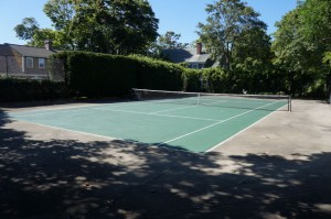 Cape Cod Painter displays a freshly painted green tennis court with bright white lines.